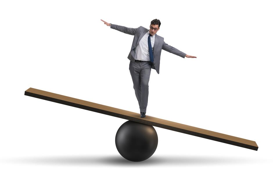 Balancing Businessman on Seesaw